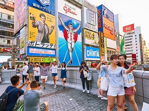 Khách du lịch tạo dáng với Glico Running Man. Tấm biển được tân trang lần gần nhất là từ năm 2014. Ảnh:ATMX.